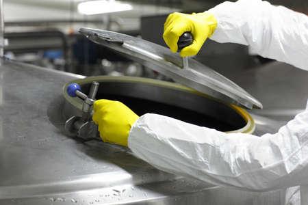 industriale: mani in guanti gialli apertura del serbatoio di processo industriale - alto vicino