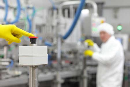 industriale: mano in giallo guanto premendo il pulsante - a partire dei processi industriali