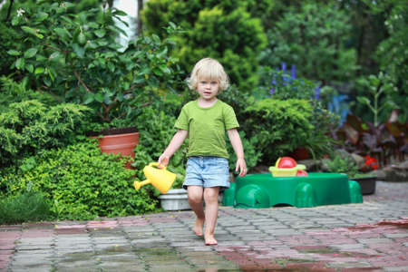 little barefoot girl with watering can - portrait photo