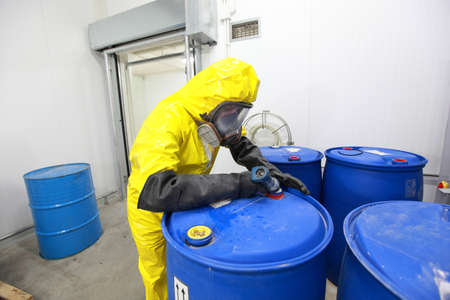 riesgo quimico: Profesional en barricas de llenado uniformes con productos químicos