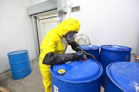 Professional in uniform vullen vaten met chemicaliën Stockfoto