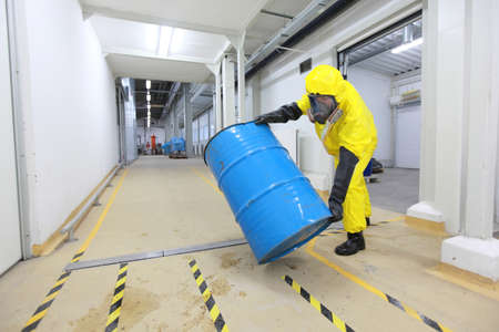 hazardous waste: technician in uniform rolling barrel with hazardous substance