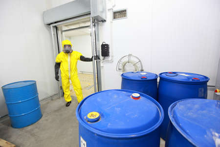 hazardous: worker in protective uniform checking barrels with toxic subsatnce in plant