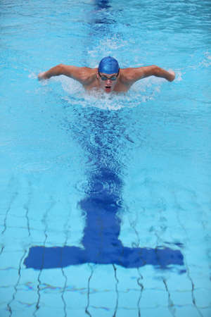 swimming race: dynamic and fit swimmer in cap breathing performing the butterfly stroke