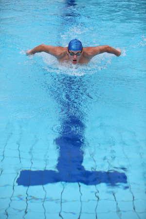 dynamische und Fit Schwimmer in Cap Atmung durchführen der Schmetterling Schlaganfall Lizenzfreie Bilder