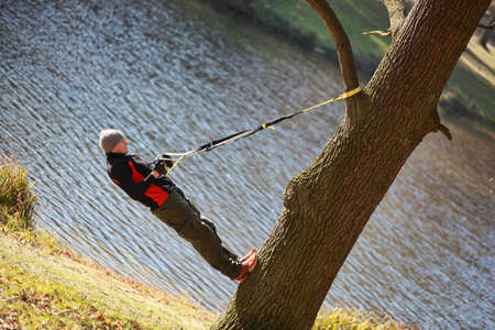 bank branch: suspension workout on tree - man at the outdoor training at the river Stock Photo