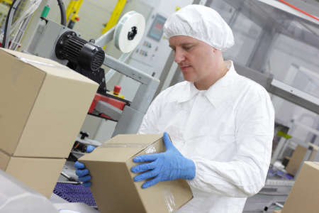 packer: White male  worker working on packing line in factory Stock Photo
