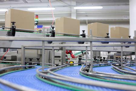 cinta transportadora: Cajas de cartón en la banda transportadora en una fábrica Foto de archivo