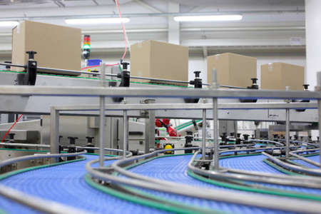automatic machine:  Cardboard boxes on conveyor belt in factory Stock Photo