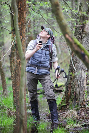 hike: lost hiker in forest with mobile satelite navigation device  - geo-caching Stock Photo