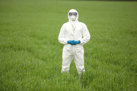 scientific farming: biotechnology engineer in white uniform, mask, goggles on field of genetically modified crops portrait