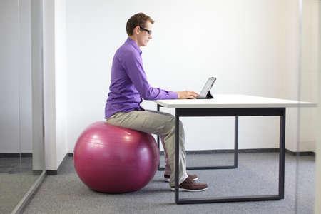hombre sentado: hombre en la bola de la estabilidad de trabajo con la tableta - la posición correcta sentado en estación de trabajo