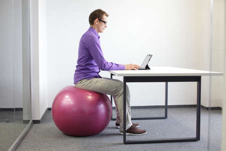 man on stability ball working with tablet - correct sitting position at workstation   photo
