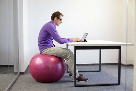 悪い姿勢のタブレット - ビジネスの男彼のオフィスでの安定性ボールの上で