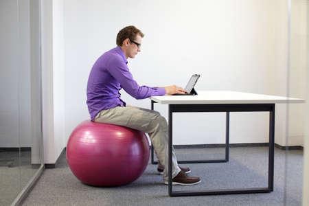 schlechten Sitzhaltung am tablet - Business-Mann auf Gymnastikball in seinem Büro