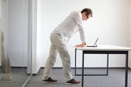 Handgelenke ausüben Durring Büroarbeit - stehender Mann Lesung in Tablette in seinem Büro