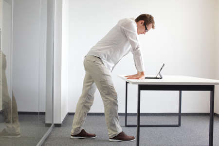 working: wrists exercise durring office work - standing man reading at tablet in his office