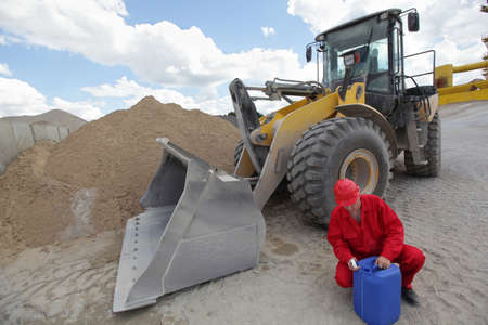 heavy equipment operator: operator in red uniform checking petrol can, large bulldozer in background