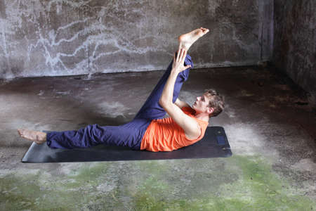 centering: fusion of mind and body - caucasian man on mat practicing pilates