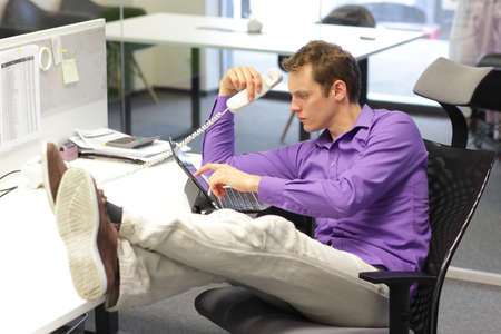 bad guy: Young businessman caucasian in his office on phone working with tablet - bad sitting posture  Stock Photo