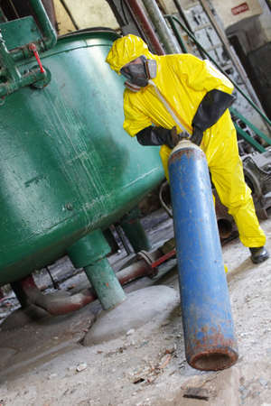 compressed: technician in yellow protective uniform, mask, and gloves dealing with steel cylinder with gas