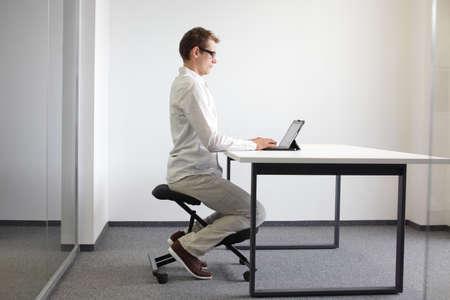 ひざまずく椅子にタブレット男とデスクで正しい座位