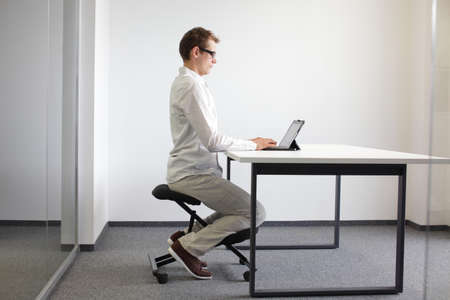 richtige Sitzposition am Schreibtisch mit Tablet-Mann auf Stuhl kniend Lizenzfreie Bilder