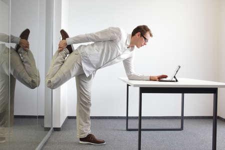 Beintrainingseinheit durrng Büroarbeit - stehender Mann Lesung in Tablette in seinem Büro