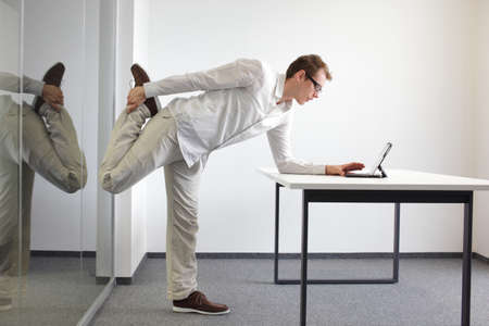 estiramientos: ejercicio de la pierna durrng trabajo de oficina - de pie la lectura del hombre en la tableta en su oficina