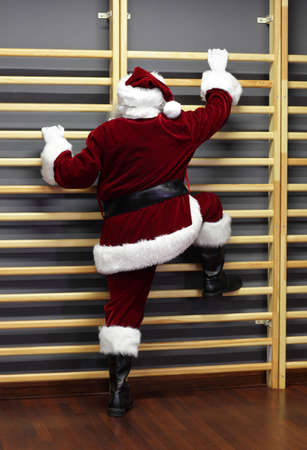 wall bars: santa claus exercising with wall bars - Christmas Time form preparation Stock Photo