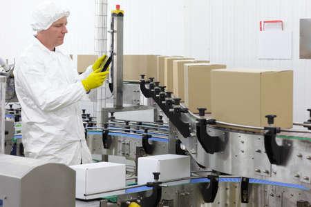 cinta transportadora: cauc�sico hombre trabajador de delantal blanco, gorro y guantes azules con el tablet, en la l�nea de producci�n en f�brica