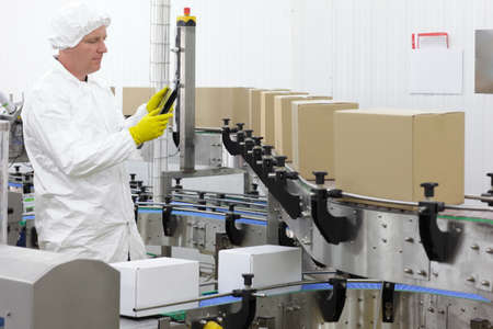 conveyor: caucasian man worker in white apron, cap and blue gloves  with tablet, at production line in factory