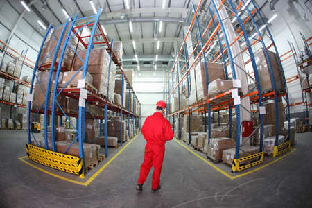 storage warehouse: worker in red uniform  in  warehouse in fish-eye lens - back view Stock Photo
