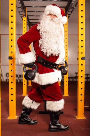 Santa Claus preparing for Christmas in gym - kettlebells training