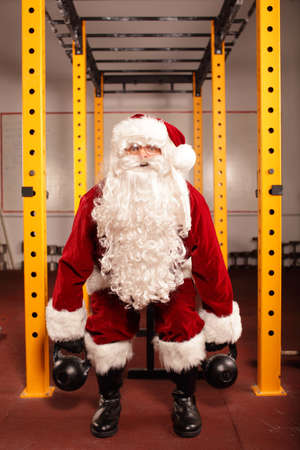 Santa Claus training before Christmas in gym - kettlebells  Stock Photo