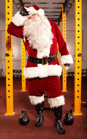 Sweating, tired Santa Claus having break in training in gym photo