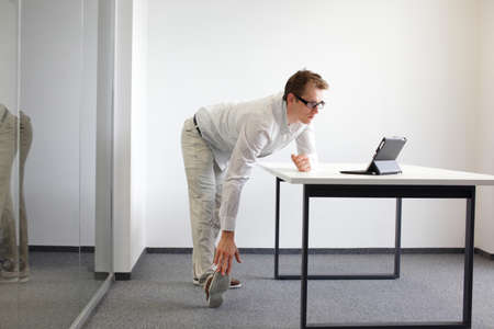 leg - arm exercise durng office work Stock Photo