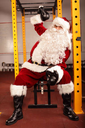 Santa Claus training before Christmas with kettlebells on bench in gym photo