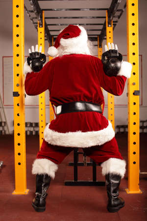 Santa Claus training before Christmas in gym - kettlebells, back view Stock Photo