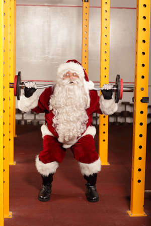 knee bend: Santa Claus  lifting weights in gym - physical condition training before Christmas