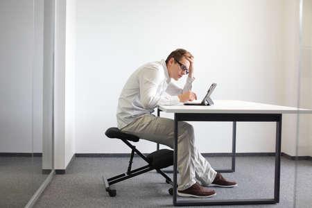 Junger Mann sucht über die Tablette in seinem Büro gebogen, Sitzplätze auf Stuhl kniend Bat Sitzhaltung bei der Arbeit