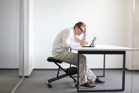 Young man is bent over her tablet in his office,seating on kneeling chair  Bat sitting posture at work  Stock Photo