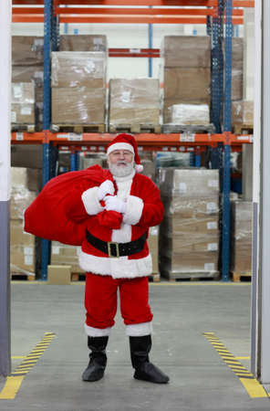 commercialization: Santa Claus after shopping,ready for Christmas,leaving storehouse with large sack full of presents