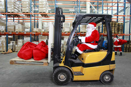 Rush hours in storehouse before Christmas time,Two santa clauses as a workers preparing sacks with gifts  One on forklift, another is lifting sacks full of presents