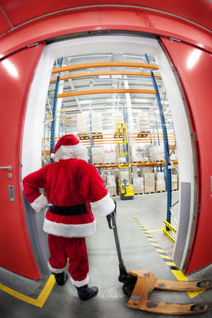 commercialization: Santa Claus with empty hand powered pallet jack at the gate to gift distribution center  Stock Photo