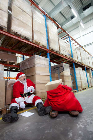 Overworked santa claus with pain in chest with list of gifts to buy in storehouse  photo