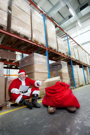 commercialization: Santa claus checking list of presents in storehouse