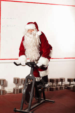 Santa Claus training on exercise bikes at the gym photo