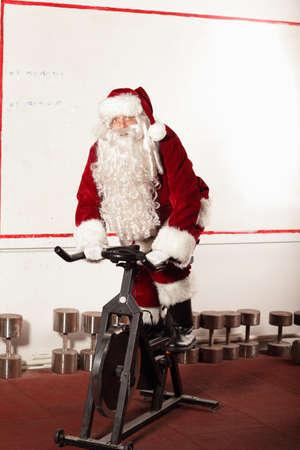 santa: Santa Claus training on exercise bikes at the gym