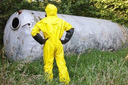riesgo quimico: técnico en uniforme que examina gran tanque de acero